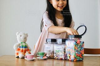 テーブルの上のお菓子を食べる女の子の写真・画像素材[2868330]