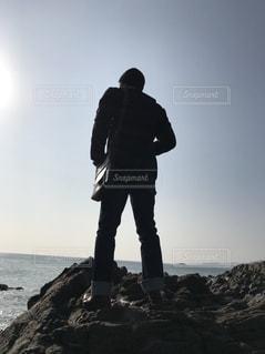 岩だらけの丘の上に立っている男の写真・画像素材[2176503]