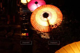 開いた傘を持った暗い部屋の明るい光の写真・画像素材[2185354]