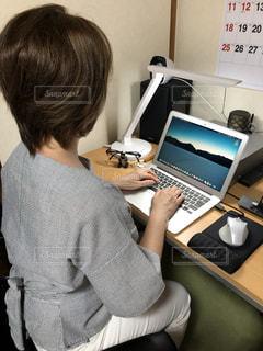 ラップトップコンピュータの前の机に座っている人の写真・画像素材[2337369]