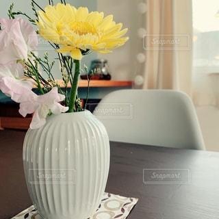 テーブルの上に座っている花で満たされた花瓶の写真・画像素材[2738084]