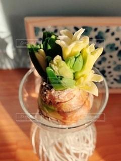 木製のテーブルの上に座っている花で満たされた花瓶の写真・画像素材[2738092]