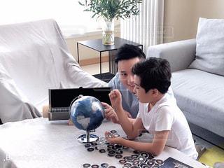 ベッドの上に座ってラップトップコンピュータを使用している若い男の子の写真・画像素材[2198458]