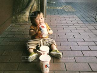 歩道に座っている小さな子供の写真・画像素材[2202790]