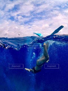 青い水の中を泳いでいる男の写真・画像素材[2329847]