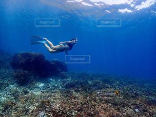 青い水の中を泳いでいる間、空を飛ぶ人の写真・画像素材[2329850]