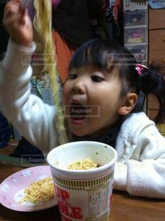 食卓に座っている小さな女の子が食べ物を食べるの写真・画像素材[2203015]