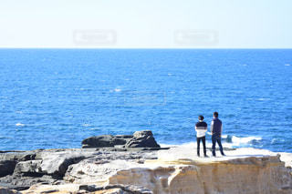 岩場のビーチに立っている男の写真・画像素材[2200401]