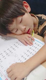 宿題しながら寝た息子の写真・画像素材[2485295]