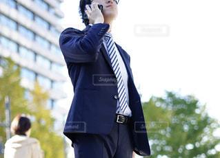 外出中電話をするスーツの営業マンの写真・画像素材[1665492]