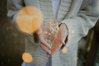 冬のファッションで、キラキラジュエリーライトの入った瓶を大切そうに持つ女性の写真・画像素材[2732580]