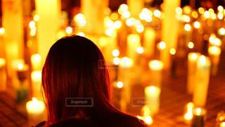 キャンドルの暖かな光を見つめる女性の後ろ姿の写真・画像素材[2793586]