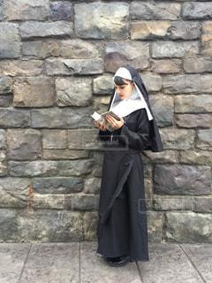 レンガの壁の前に立つ男が携帯電話で話しているの写真・画像素材[2500269]