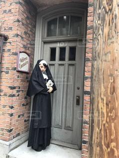 レンガ造りの建物の前に立っているシスターの写真・画像素材[2500272]