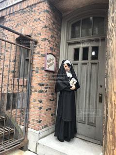 レンガ造りの建物の前に立っているシスターの写真・画像素材[2502952]