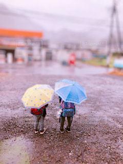 傘を持って雨の中に立っている小さな男の子の写真・画像素材[2208881]