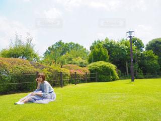 背景に木がある緑の野原の人の写真・画像素材[2260332]