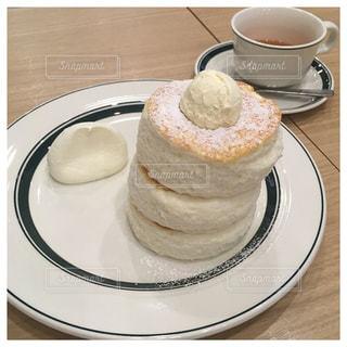 コーヒー1杯の隣の皿の上のケーキの写真・画像素材[2279415]