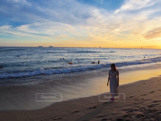 水域の近くの浜辺に立っている人の写真・画像素材[2328653]