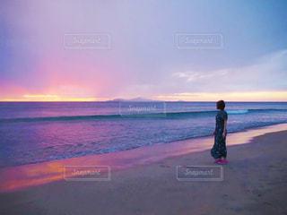 水域の近くの浜辺に立っている男の写真・画像素材[2377280]