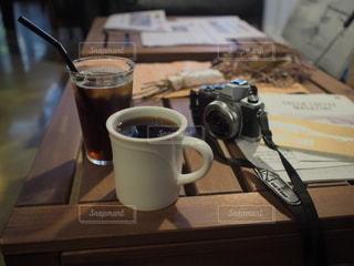 テーブルの上にはコーヒーとカメラの写真・画像素材[2891476]
