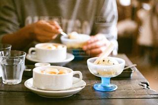 コーヒーを飲みながらテーブルに座っている人の写真・画像素材[2261563]