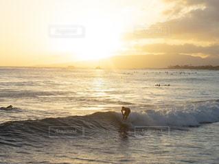 海でサーフィンをしている男性と夕日の写真・画像素材[2376212]