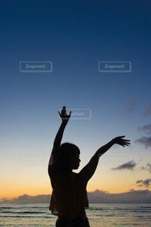 ハワイの夕日と女性の写真・画像素材[2376226]