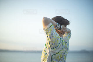 海辺から夕日眺める女性の写真・画像素材[2376247]
