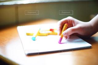 木製の机の上で、絵を描いている女性の手の写真・画像素材[2382142]