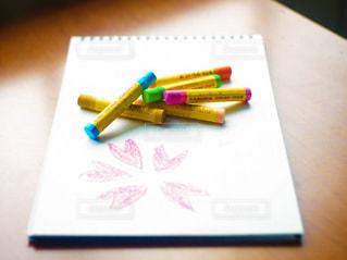 教室の机に置いてある画用紙とクレヨンの写真・画像素材[2382152]