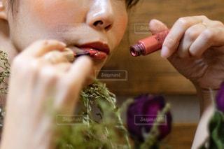 リップグロスを塗っている女性の唇の写真・画像素材[2394830]