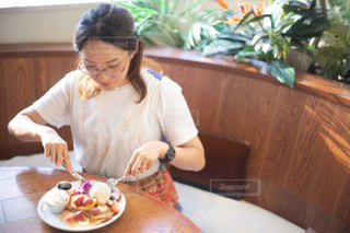 食べ物の皿を持ってテーブルに座っている女性の写真・画像素材[2407989]