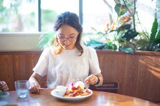 窓の前のテーブルに座っている女性の写真・画像素材[2407995]