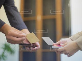 名刺交換をする段差と女性の手の写真・画像素材[2425116]