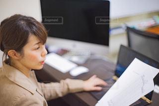 机の上に座っているノートパソコンで仕事をする女性の写真・画像素材[2425124]