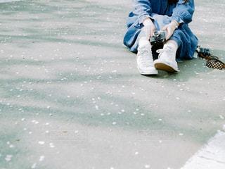 道路に座っている、フィルムカメラを持った青のワンピースの女性の写真・画像素材[2432851]