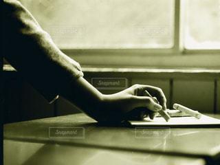 机の上にあるクレヨンを持って絵を描く女性の手(モノクロ)の写真・画像素材[2433193]