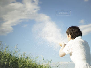 青空の下で手から雲を出している女性の写真・画像素材[2473221]
