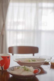 テーブルの上に置かれた朝食とマグカップの写真・画像素材[2492821]