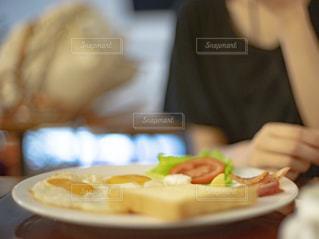 プレート上の朝食を食べる人物の写真・画像素材[2495441]