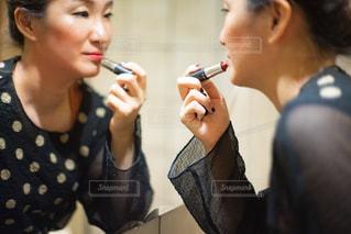 ドレッサーの前でメイクをする女性の写真・画像素材[2511875]