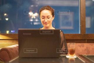 テーブルに座ってノートパソコンで仕事をしているいる女性の写真・画像素材[2535829]