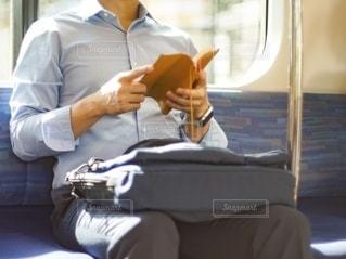 電車で本を読む男性の写真・画像素材[2629577]