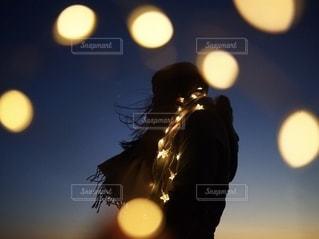 夜にライトに包まれて立っている女性の写真・画像素材[2661163]