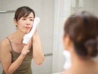 顔をタオルで拭く鏡越しの女性の写真・画像素材[2721970]
