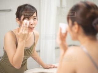 鏡の前で化粧を落とす女性の写真・画像素材[2721975]