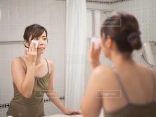 鏡の前でメイク落としをする女性の写真・画像素材[2721979]