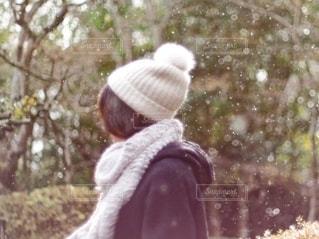 雪の中ニット帽をかぶっている女性の後ろ姿の写真・画像素材[2731604]