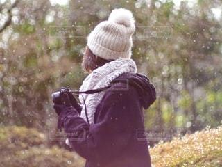 雪の中ニット帽をかぶって写真を撮る女性の写真・画像素材[2731627]